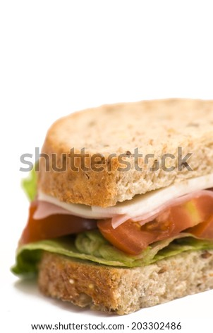 Sandwich  of cheese, ham, tomato and lettuce on white background