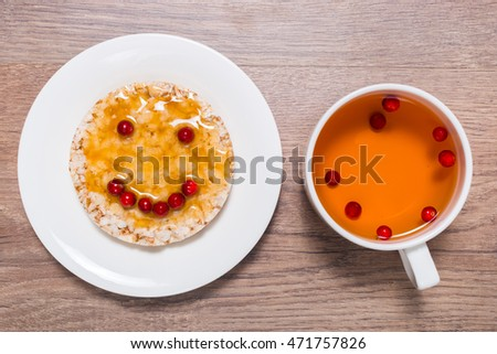 Sandwich of crispy bread, honey and cranberries on the saucer and cup with berry tea