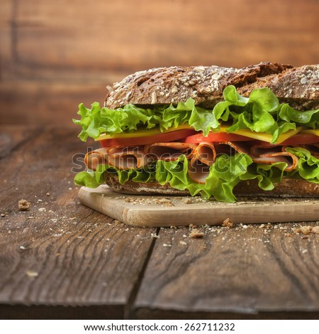 Sandwich on the wooden table with slices of fresh tomatoes, ham, cheese and lettuce - stock photo