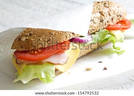 Sandwich on white paper - stock photo