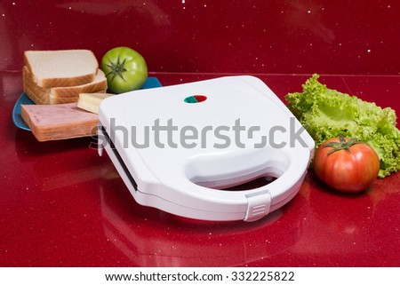 Sandwich Toaster with ingredients in a kitchen setting - stock photo