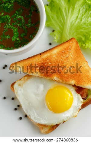 Sandwich with a fried egg and a mug of soup on a white plate with lettuce leaves and black pepper, close-up view from above - stock photo