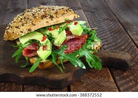 Sandwich with arugula, salami and avocado