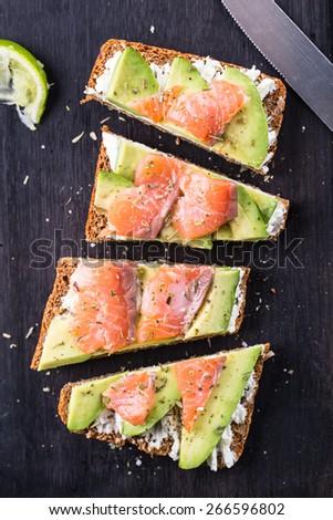 Sandwich with avocado and smoked salmon - stock photo