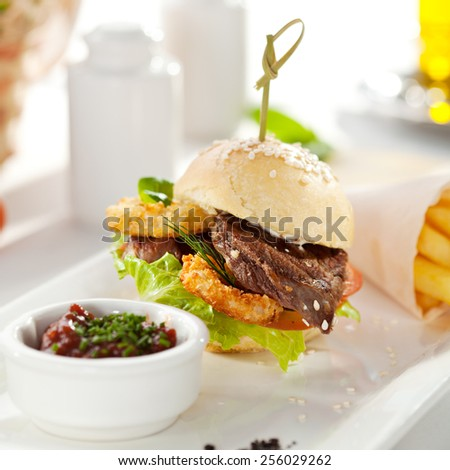 Sandwich with Beef and Deep Fried Onions Ring, Tomato and Cucumber. Garnished with French Fries - stock photo