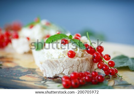 sandwich with cheese and red currants on a wooden table