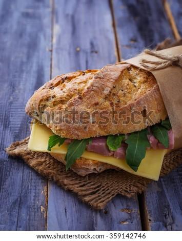 Sandwich with cheese, arugula, ham. Selective focus - stock photo
