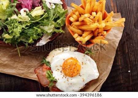 Sandwich with cheese bacon and fried egg on wooden background