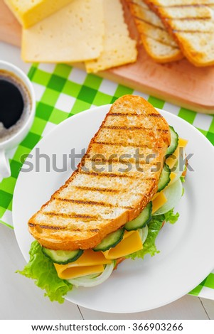 Sandwich with cheese, lettuce and vegetables for breakfast with coffee, top view - stock photo