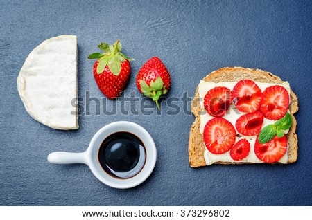 Sandwich with cheese, strawberries and balsamic vinegar on a black background. toning. selective focus - stock photo