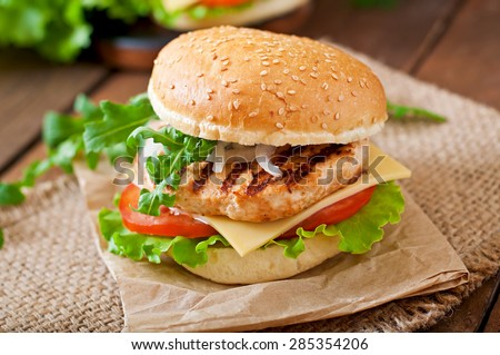 Sandwich with chicken burger, tomatoes, cheese and lettuce - stock photo