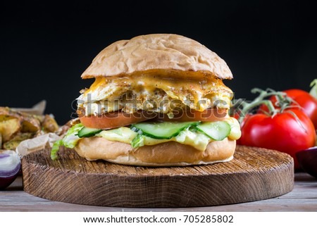 Sandwich with chicken burger, tomatoes, cheese and lettuce on wooden table. Tasty and appetizing hamburger with chicken