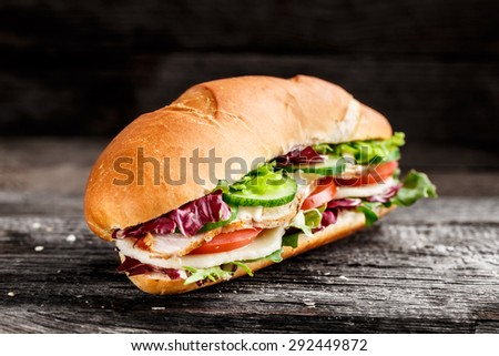 Sandwich with chicken, cheese and vegetables - stock photo