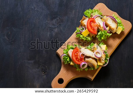 Sandwich with chicken, salad, onion and tomato on dark background. Selective focus. Top view, space for text - stock photo