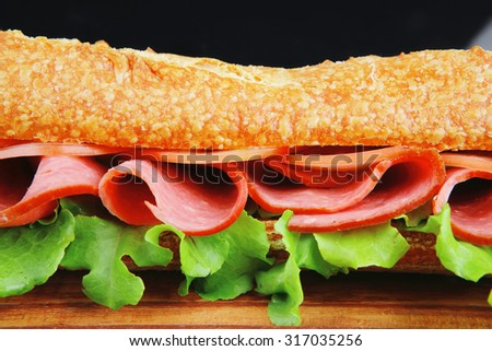 sandwich with chicken smoked sausage on wood over black background