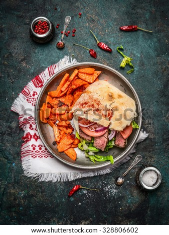 Sandwich with ciabatta bread , roasted meat, vegetables and sweet potato in plate on rustic wooden background, top view - stock photo