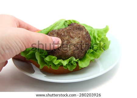sandwich with cutlet and leaf lettuce in hand - stock photo