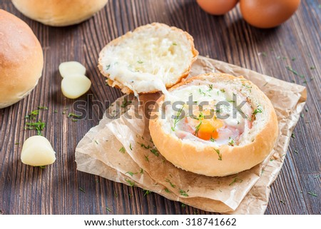 Sandwich with egg, cheese and bacon. Hot breakfast. Bun with liquid egg, bacon and melted cheese on dark wooden background - stock photo
