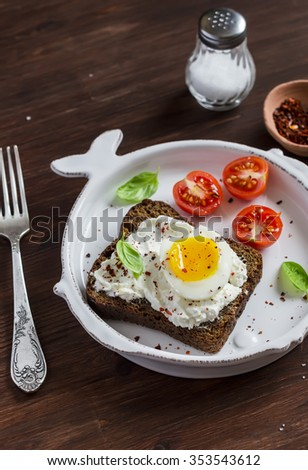 Sandwich with feta cheese and boiled egg, tomatoes, and basil on a white plate on a dark wooden surface. Healthy breakfast or snack