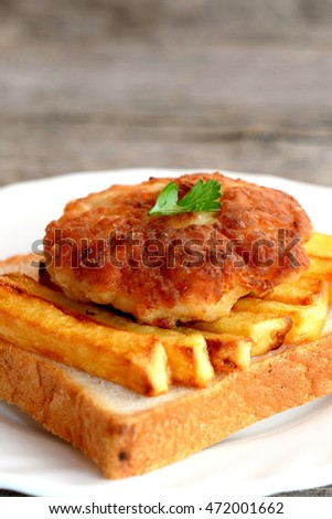 Sandwich with fried potatoes and Turkey meat cutlet on a plate and on old wooden table. A sandwich cooked from white bread, fried potatoes and Turkey burger. Closeup