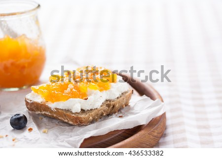 Sandwich with fruit jam and cottage cheese on a white plate, closeup with copy space