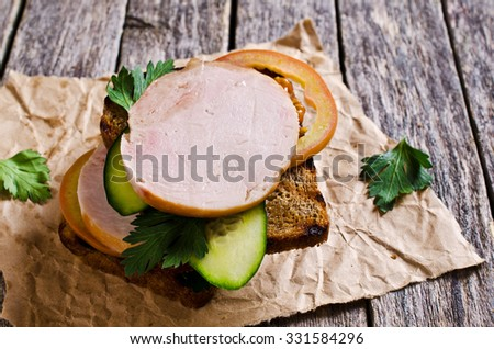 Sandwich with ham and vegetables on dark bread. Selective focus. - stock photo