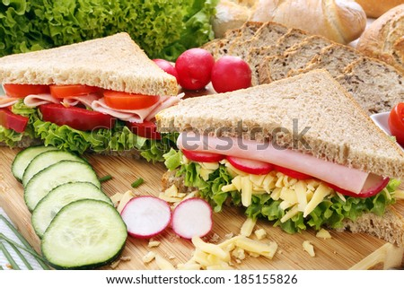 Sandwich with ham, cheese and radish on wood background - stock photo