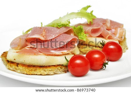 sandwich with  ham, fresh pear and cherry tomatoes on white plate