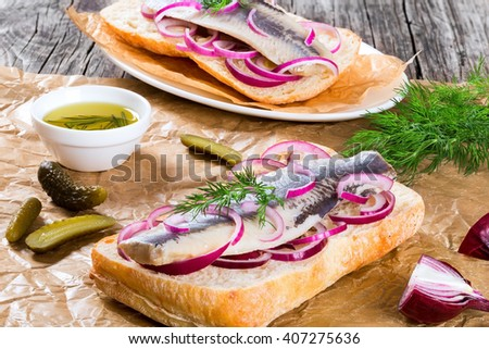 sandwich with herring fillets, onion, pickled cucumber and dill on parchment paper on an oval dish on old rustic table, traditional street food in norway, close-up  - stock photo
