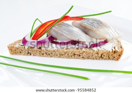 Sandwich with marinated atlantic herring bites on a rye bread - stock photo
