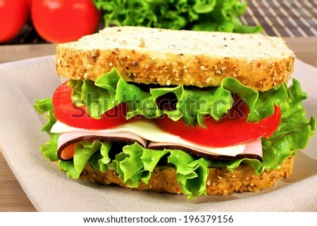 Sandwich with meat, tomato, lettuce and cheese on whole grain bread