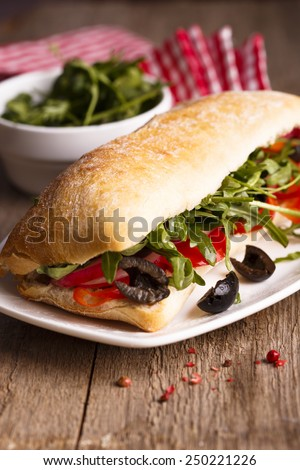 Sandwich with olives, bell pepper and arugula - stock photo
