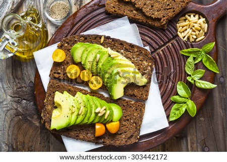 sandwich with rye bread on a board for cutting: avocado, yellow tomatoes, pine nuts and basil leaves. grated black pepper and olive oil. on the old wooden background. - stock photo