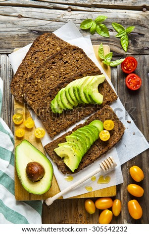 sandwich with rye bread on old wooden table. with avocado and colorful cherry tomatoes. - stock photo