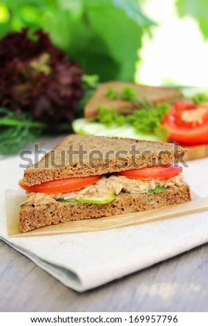 Sandwich with rye brown bread, ripe tomatoes, cucumbers and tuna fish for healthy snack - stock photo
