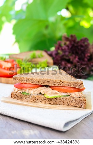 Sandwich with rye brown bread, ripe tomatoes, cucumbers and tuna fish for healthy snack on a napkin on a wooden table, selective focus - stock photo