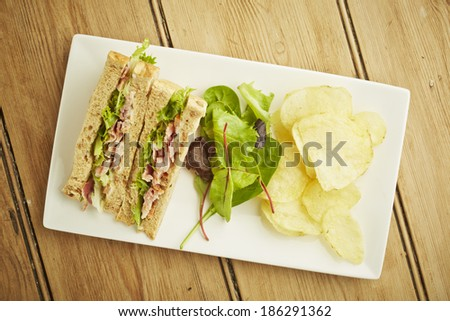 Sandwich with salad and potato chips on white dish and wooden table top - stock photo