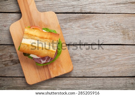 Sandwich with salad, ham, cheese and tomatoes on cutting board. Top view with copy space - stock photo