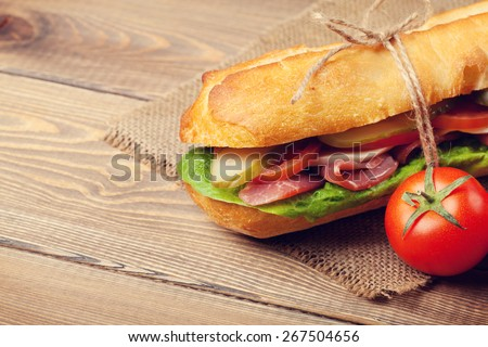 Sandwich with salad, ham, cheese and tomatoes on wooden table - stock photo