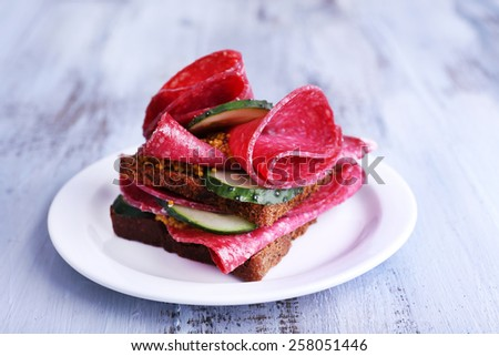 Sandwich with salami and cucumber on plate on color wooden table background - stock photo