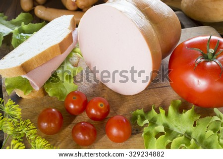 sandwich with sausage, salad and tomatoes