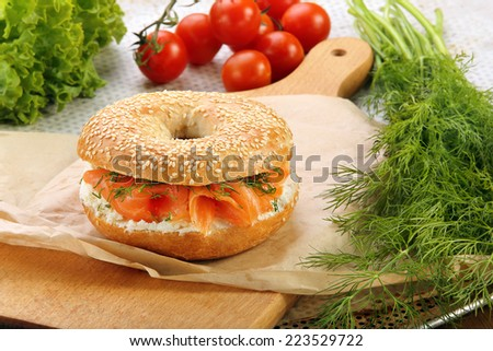 Sandwich with smoked salmon and dill on a chopping board - stock photo