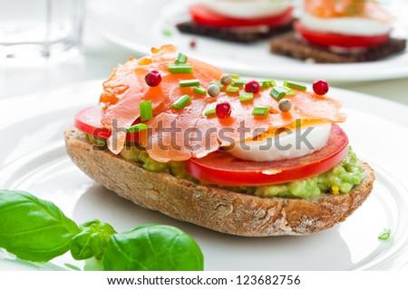 Sandwich with smoked salmon, avocado, tomato and egg - stock photo