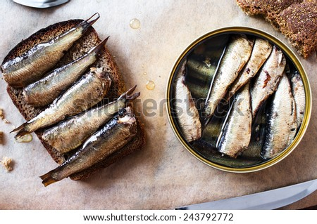 Sandwich with sprats on a table with a can of sprats - stock photo