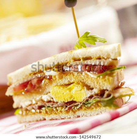 sandwich with three layers, filled with bacon eggs and vegetables - stock photo