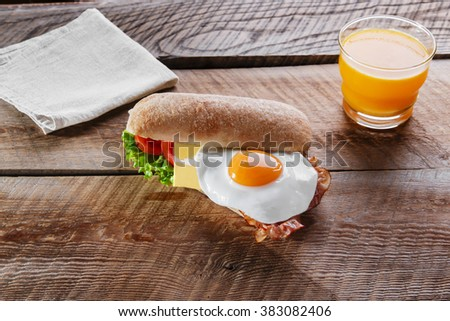 Sandwich with tomato bacon cheese and egg