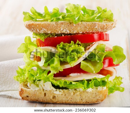 Sandwich with turkey and fresh vegetables on  wooden table  - healthy eating