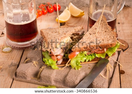Sandwich with Vegetables and Mug of Beer. Fresh and Tasty Sandwich with Roast Meat. - stock photo