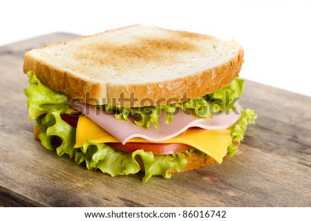 sandwich with vegetables, meat and cheese on wooden board