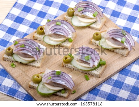 Sandwiches of white bread with fresh cucumber, cheese, herring, onions and herbs - stock photo